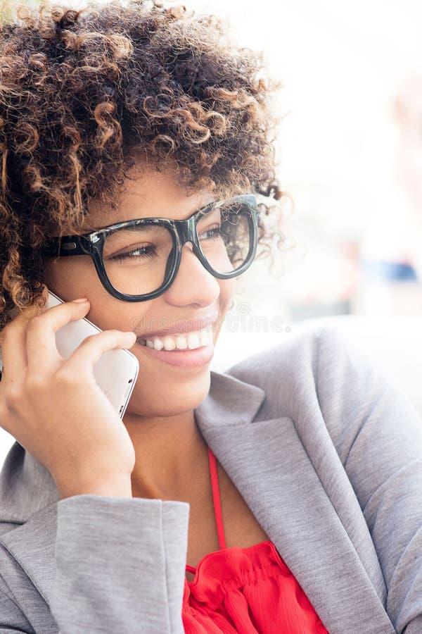 微笑的女实业家谈话由电话 免版税图库摄影