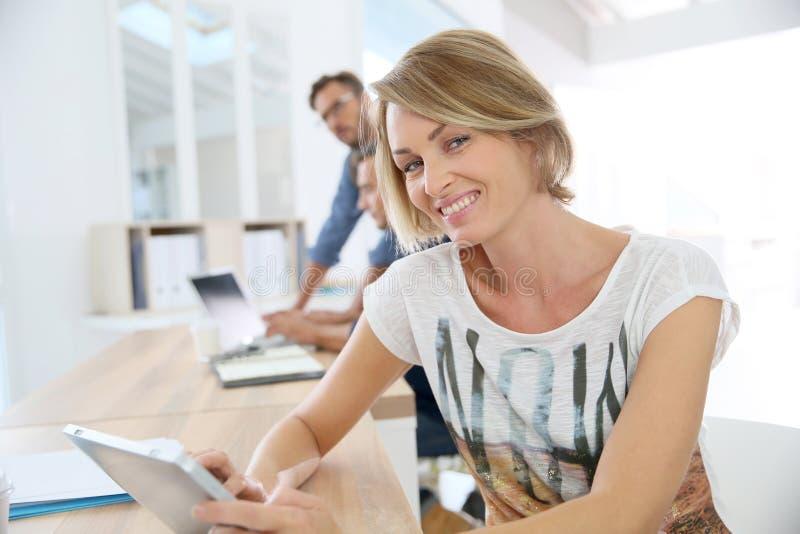 微笑的女实业家画象在有工友的办公室 库存图片