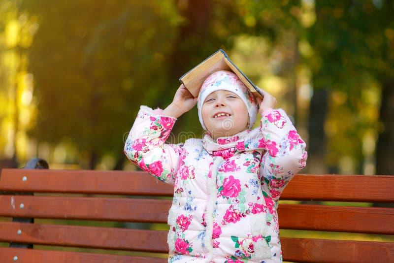 微笑的女小学生拿着在她的头的一本书 图库摄影