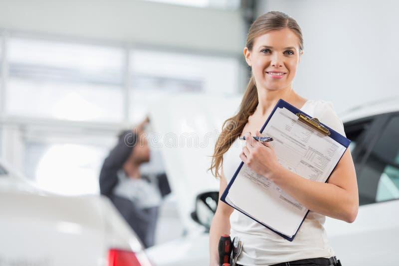 微笑的女性修理工作者画象有剪贴板的在汽车车间 图库摄影