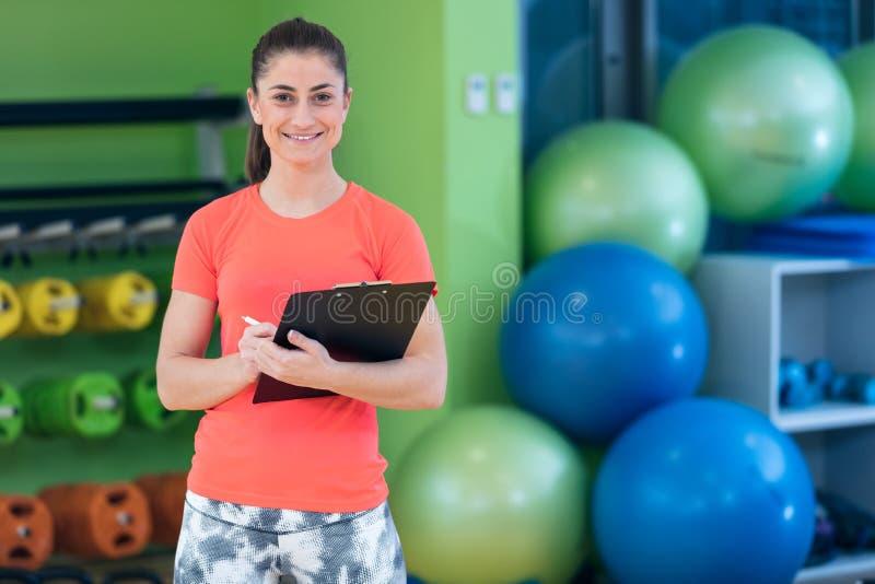 微笑的女性健身辅导员文字画象在剪贴板的,当站立在健身房时 免版税库存照片