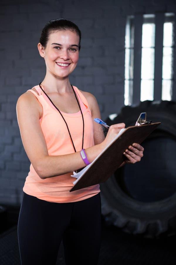 微笑的女性健身辅导员文字画象在剪贴板的 免版税库存图片