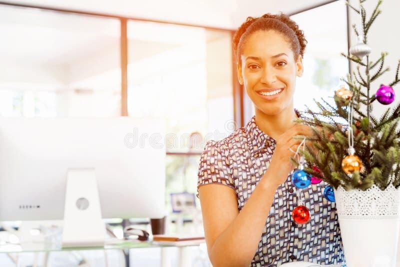 微笑的女性办公室工作者画象有圣诞树的 免版税库存图片