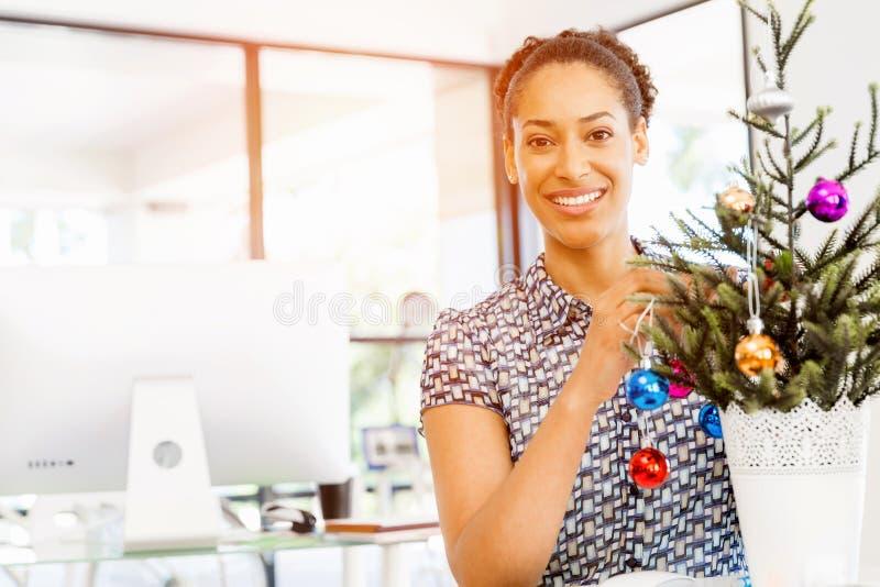 微笑的女性办公室工作者画象有圣诞树的 免版税图库摄影