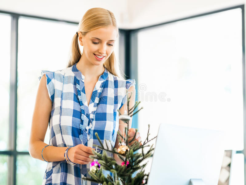 微笑的女性办公室工作者画象有圣诞树的 库存图片