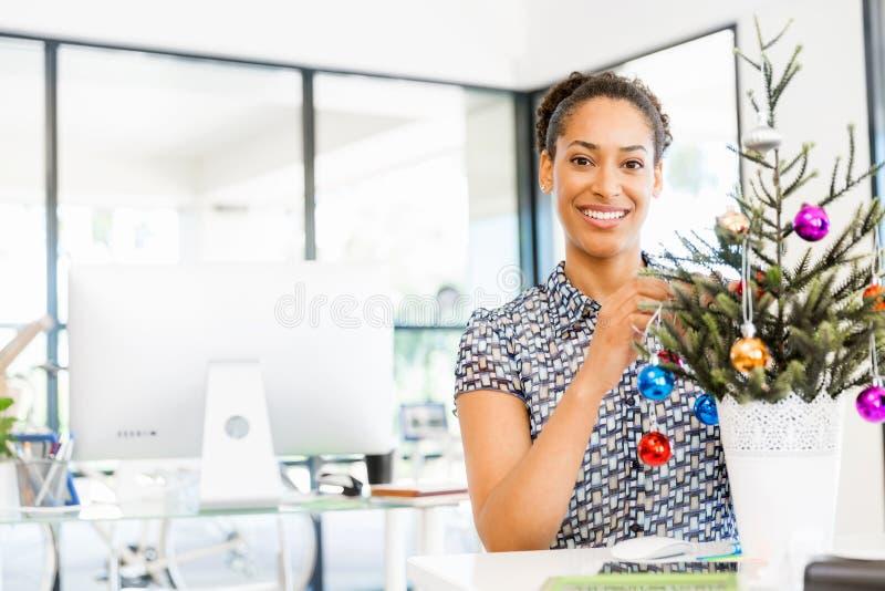 微笑的女性办公室工作者画象有圣诞树的 库存照片