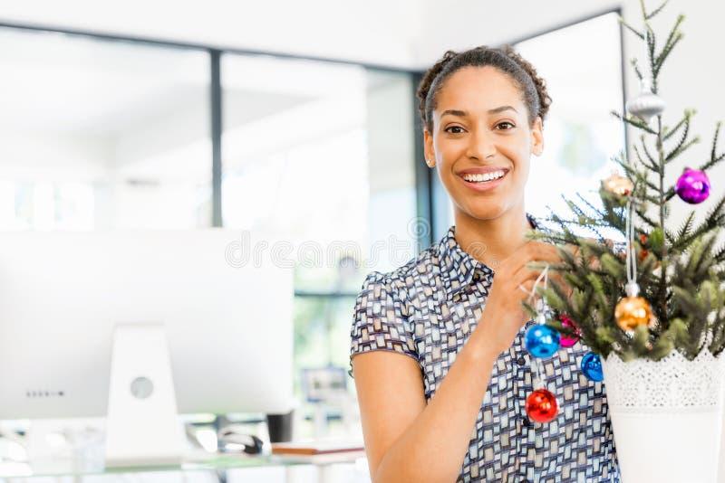 微笑的女性办公室工作者画象有圣诞树的 免版税库存照片