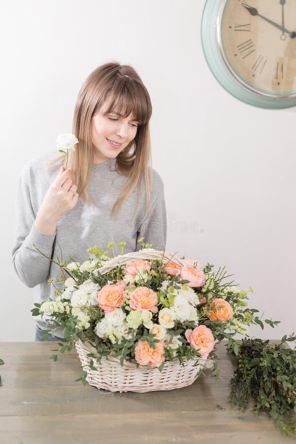 微笑的女性卖花人花卉车间-做美好的花构成在一个柳条筐的妇女花束 免版税库存图片