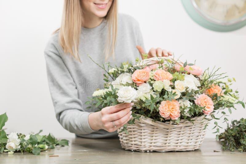 微笑的女性卖花人花卉车间-做美好的花构成在一个柳条筐的妇女花束 库存图片