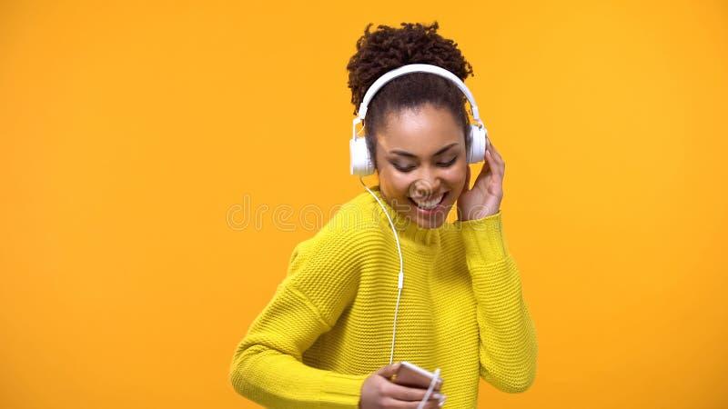 微笑的女性听在白色耳机的喜爱的曲调,技术 免版税图库摄影