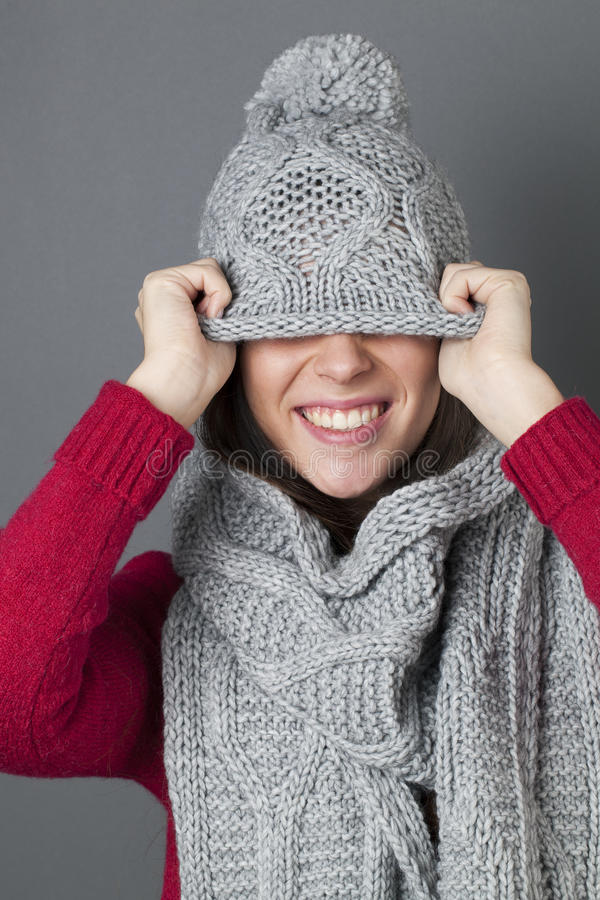 微笑的女性少年耍笑在掩藏在冬天帽子下 免版税库存照片