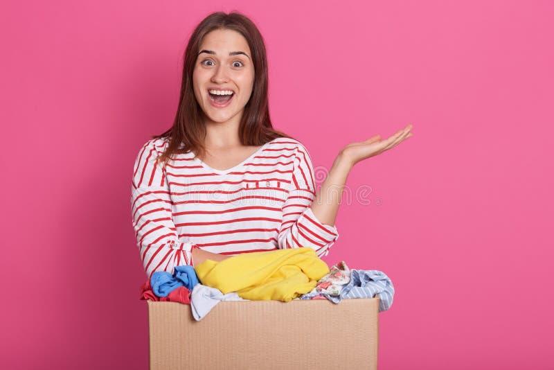 微笑的女性志愿身分画象在捐赠箱子附近的反对玫瑰色背景,采取她的手对边和保留嘴 免版税库存图片