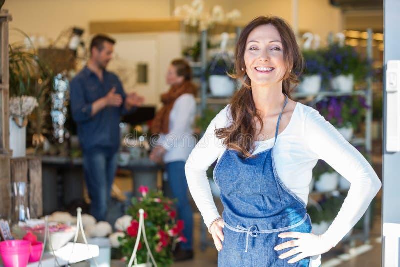 微笑的女性所有者画象在花店 免版税库存图片