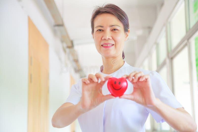 微笑的女性护士在她的手上的拿着红色微笑心脏 代表优质服务头脑的红色心脏形状对患者 免版税库存图片