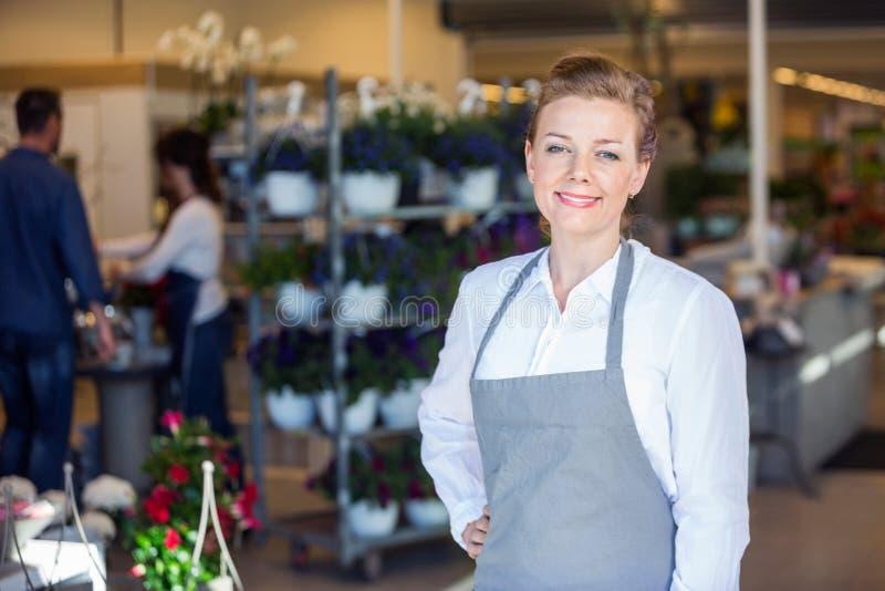 微笑的女性推销员画象花的 免版税图库摄影