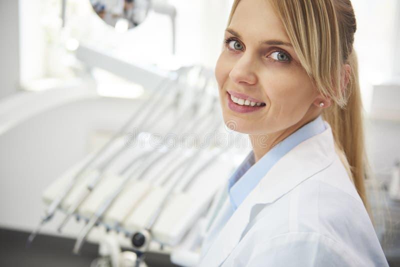 微笑的女性牙医画象在牙医的办公室 库存图片