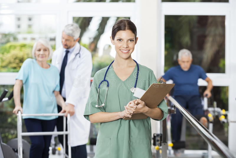 微笑的女性生理治疗师在健身分的拿着剪贴板 免版税图库摄影