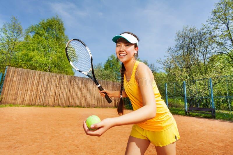 微笑的女性网球员服务室外 免版税库存图片