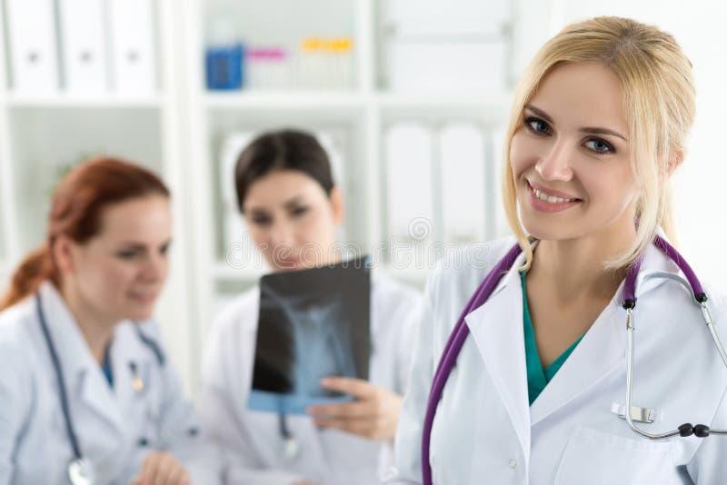 微笑的女性医学医生画象有两个同事的 库存照片