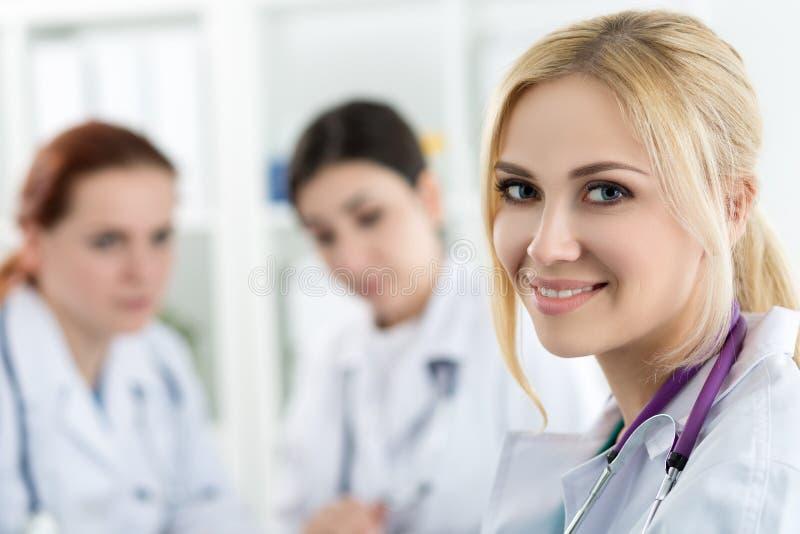 微笑的女性医学医生画象有两个同事的 免版税图库摄影