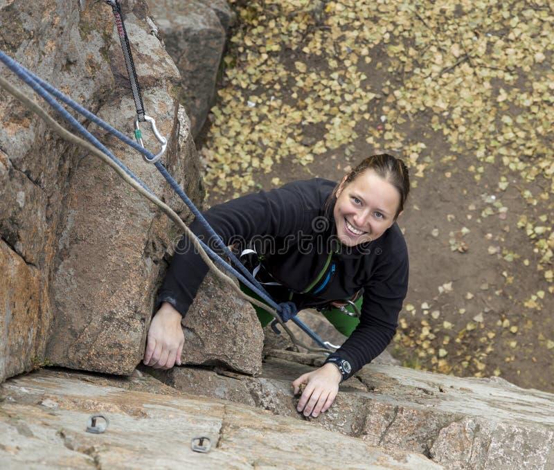 微笑的女性登山人和她的绳索 免版税库存图片