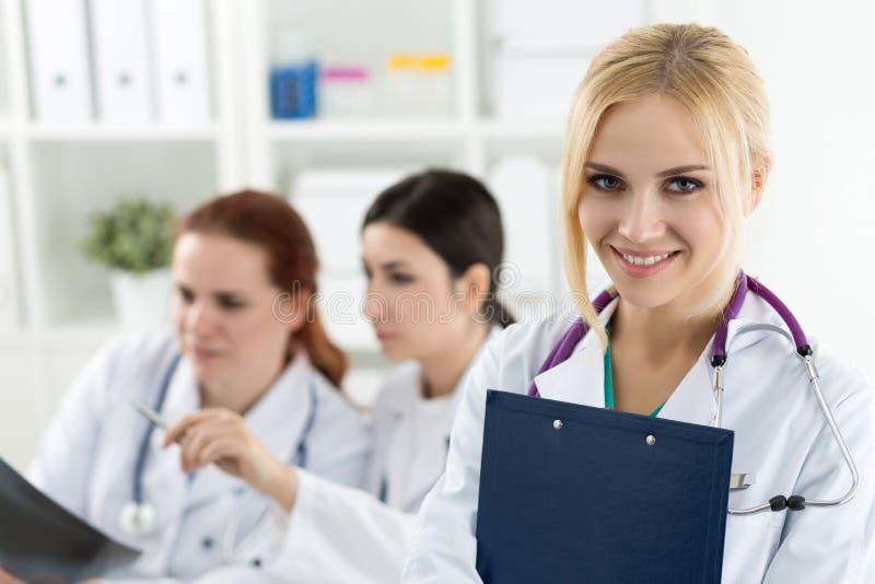 微笑的女性医生画象有两个同事的 库存图片