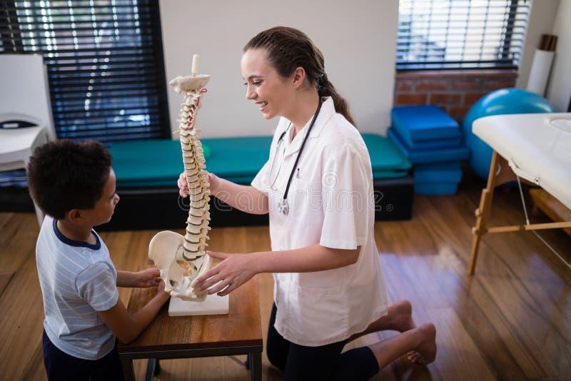 微笑的女性治疗师解释的男孩侧视图有人为脊椎的 库存图片