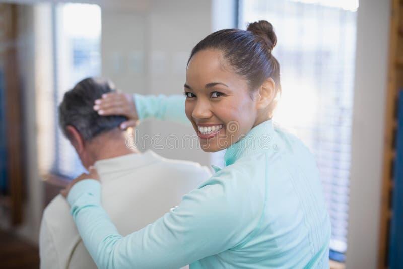 微笑的女性治疗师画象背面图给脖子的按摩资深男性患者 免版税库存照片