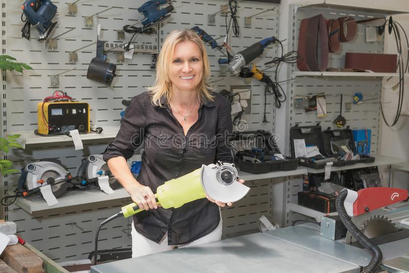 微笑的女推销员卖一台电手切割机 免版税库存照片