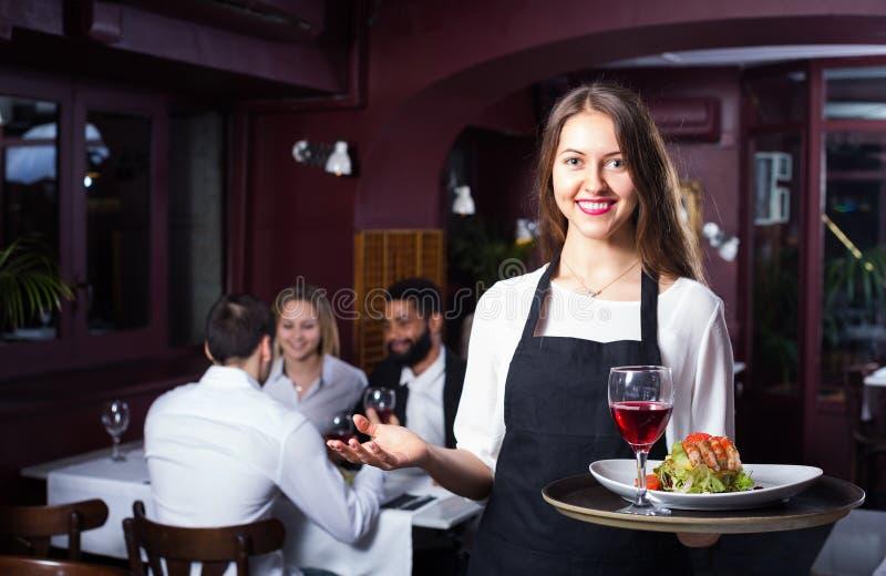 微笑的女服务员和客人在桌上 库存图片