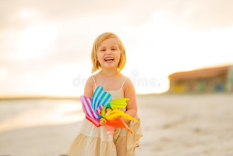 微笑的女婴画象有风车玩具的 库存照片