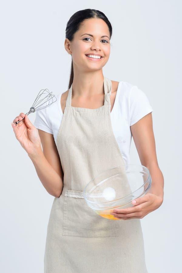 微笑的妇女与扫和烘烤的碗 免版税库存图片