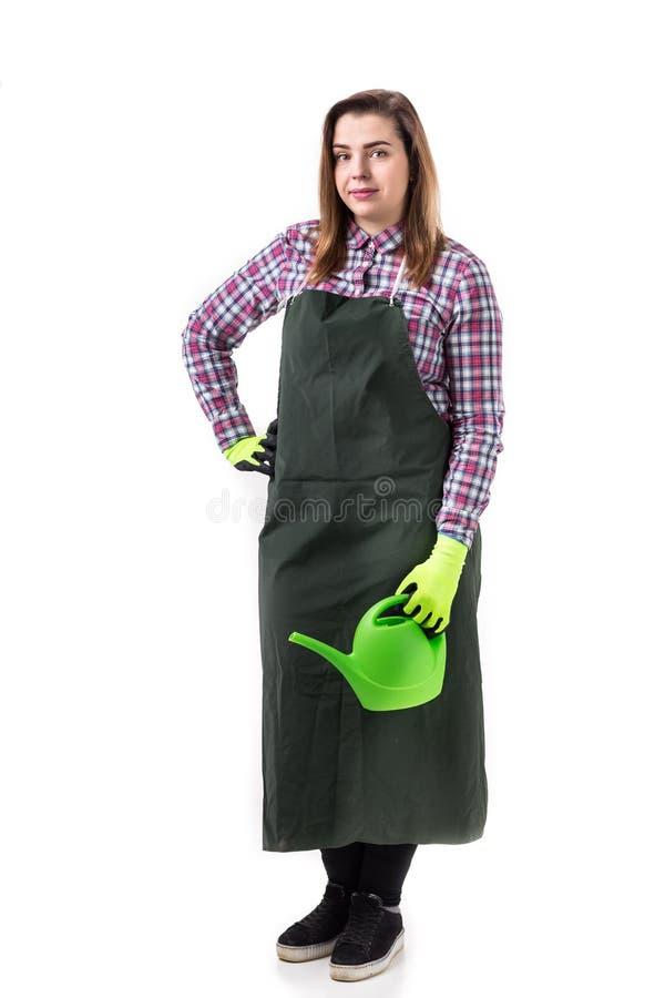 微笑的妇女专业花匠或卖花人画象拿着园艺工具的围裙的被隔绝在白色背景 库存图片