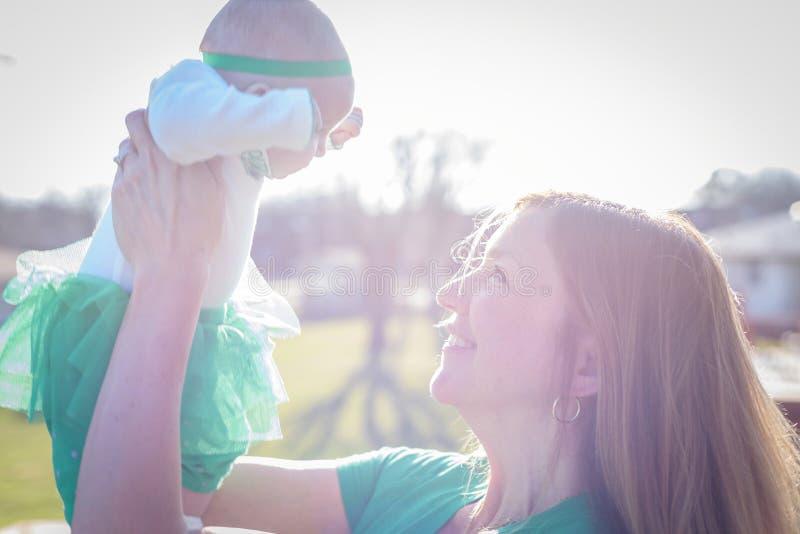 微笑的妇女举的婴孩特写镜头到明亮的阳光里 免版税库存照片
