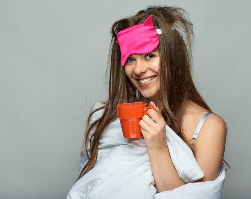 微笑的妇女佩带的睡眠掩没拿着红色咖啡杯 库存图片