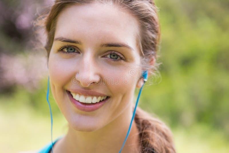 微笑的妇女佩带的耳机 免版税图库摄影