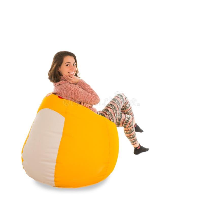 微笑的妇女侧视图坐黄色装豆子小布袋椅子isola 库存图片