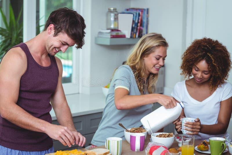 微笑的妇女倾吐的牛奶在桌上 免版税库存图片