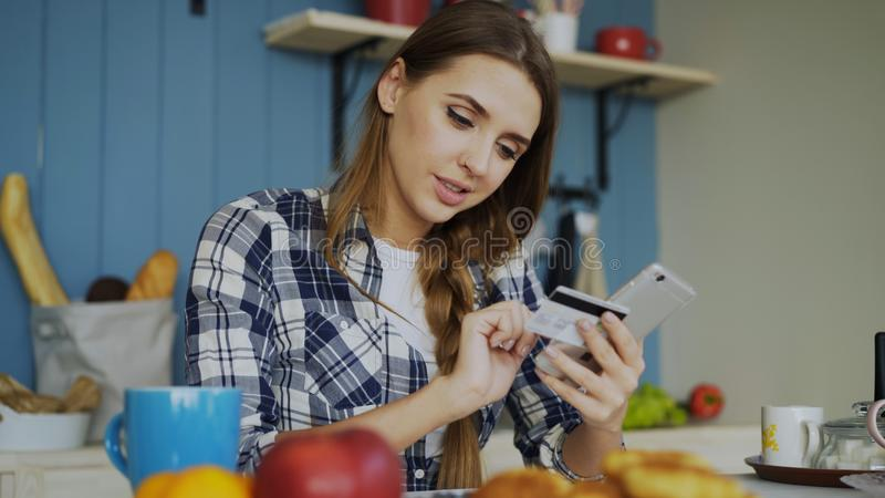 微笑的妇女做网上购物的使用智能手机和信用卡,当在家时食用早餐在厨房 图库摄影