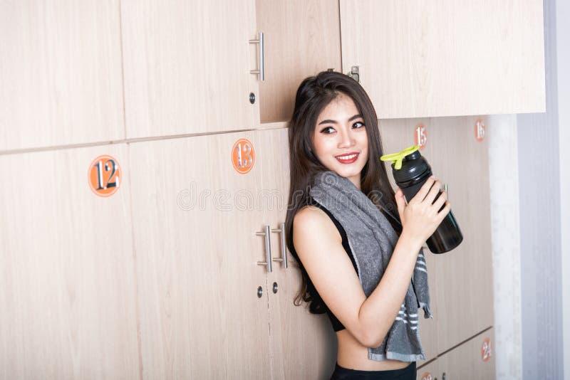 微笑的妇女准备好锻炼在健身房更衣室 免版税库存图片