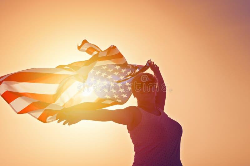 微笑的妇女剪影太阳镜的用有美国旗子的被举的手 库存照片