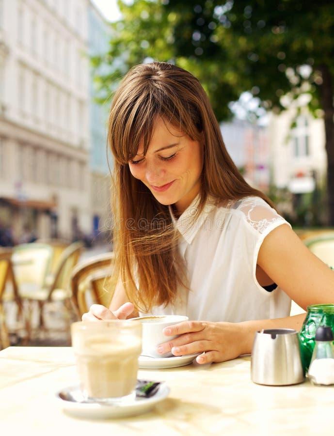 微笑的妇女喝咖啡在咖啡馆 免版税图库摄影