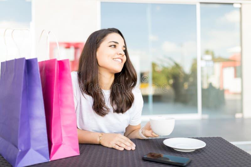 微笑的妇女喝咖啡在购物以后在咖啡馆在购物中心 免版税库存照片