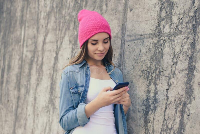 微笑的妇女在倾斜在街道墙壁和使用的便衣和桃红色帽子穿戴了互联网聊天的细胞手机的cel 免版税库存照片