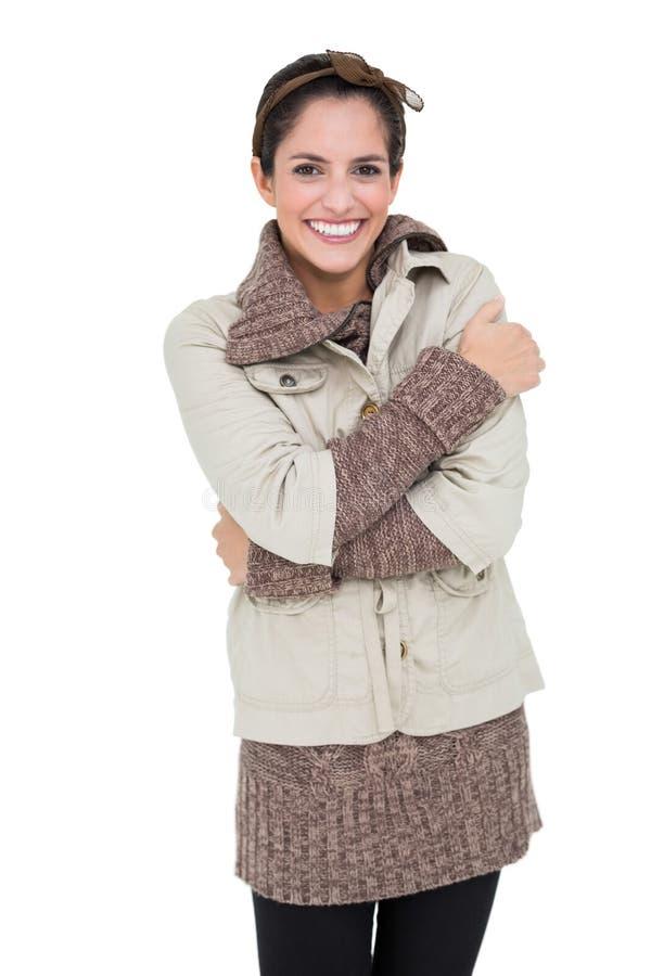 微笑的妇女在冬天塑造武装的常设十字架 免版税库存图片