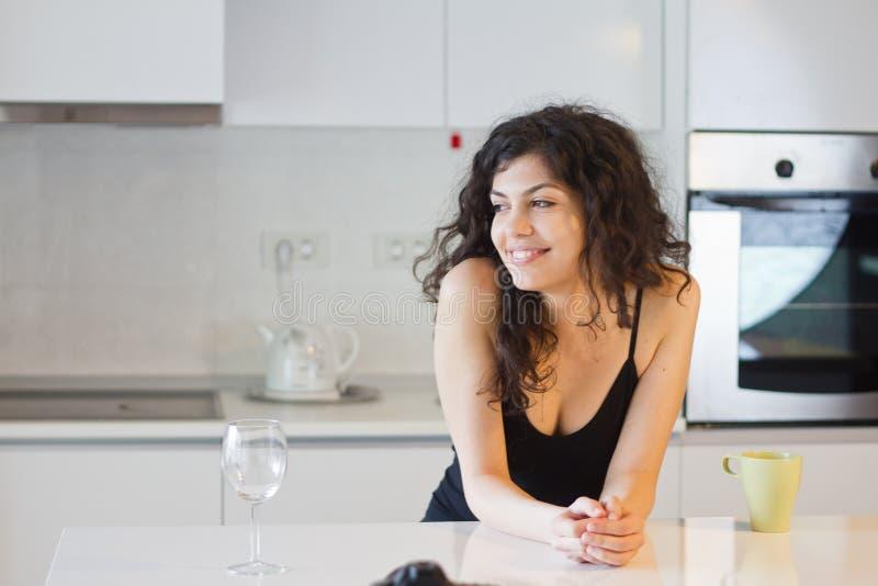微笑的妇女在厨房里 库存照片