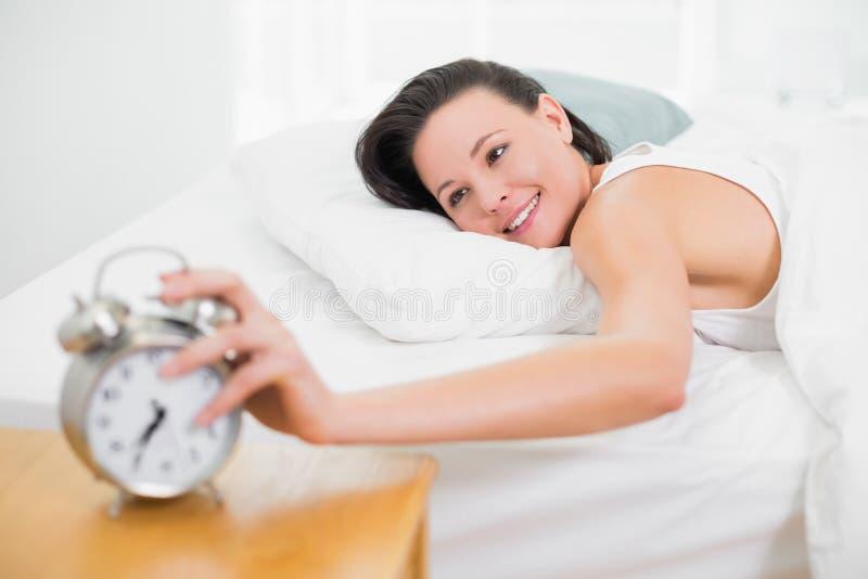 微笑的妇女在对闹钟的床延伸的手上 免版税库存照片