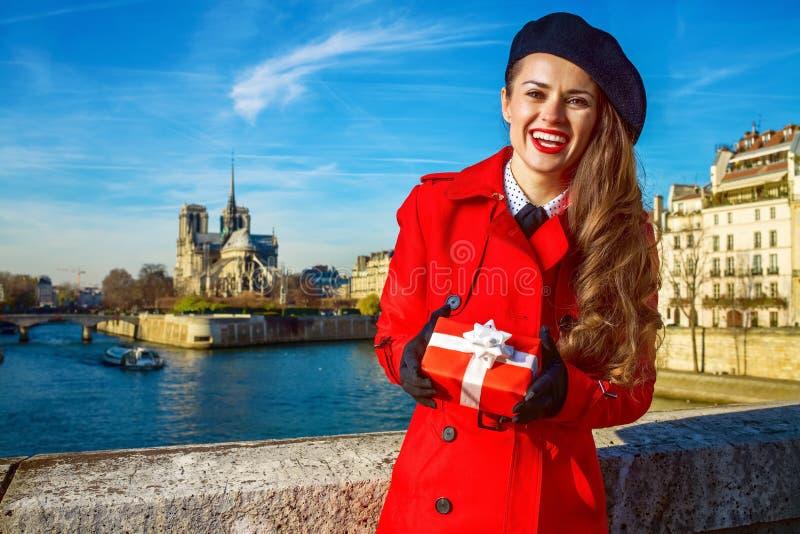 微笑的妇女在巴黎,有圣诞节礼物箱子的法国 免版税图库摄影