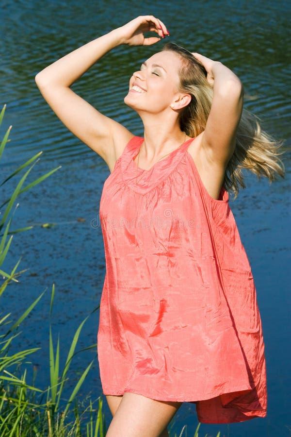 微笑的妇女在放松红色,愉快的女孩的夏天 免版税图库摄影