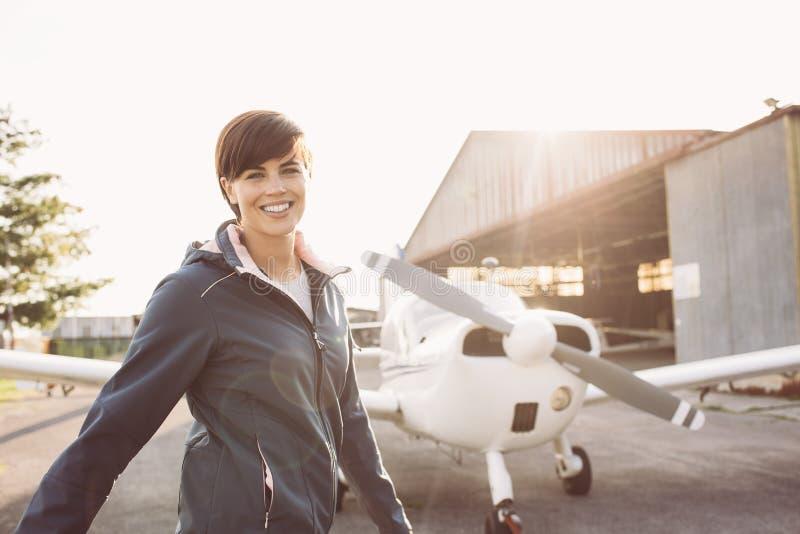 微笑的妇女在有小型飞机的机场 免版税库存图片